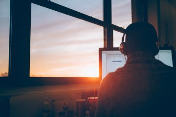 Man sitting behind computer, with headphones, and sunset in the backgrounds