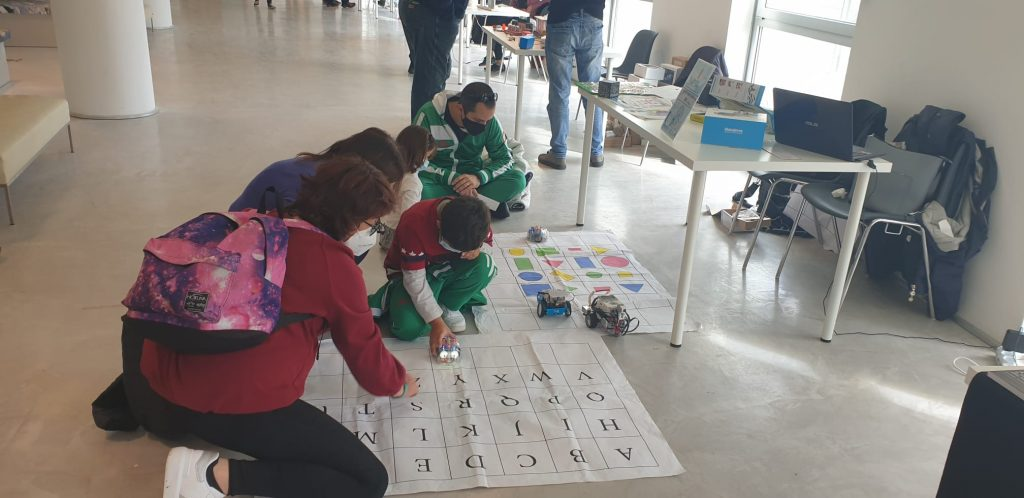 Children engaged in a playful interactive activities involving a postcard with letter and a robot.