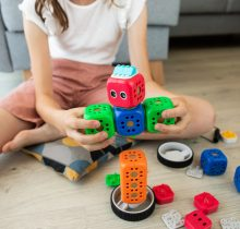 The image shows a child playing with a robot kit